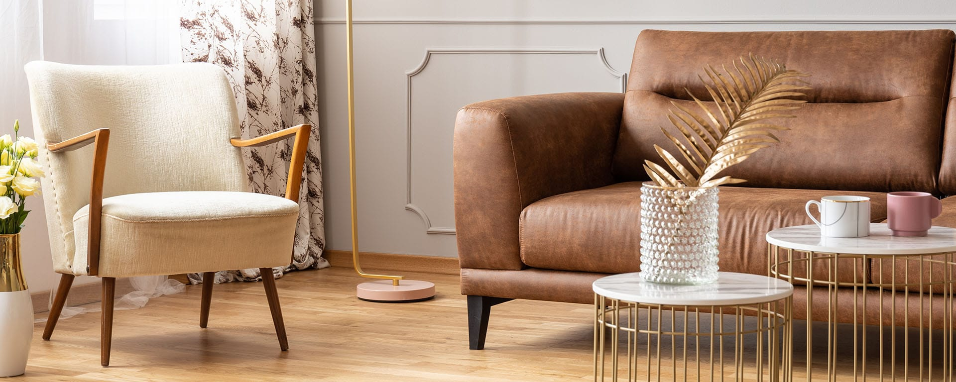 Panoramic view of living room with two small coffee tables, vintage armchair and brown leather sofa, real photo